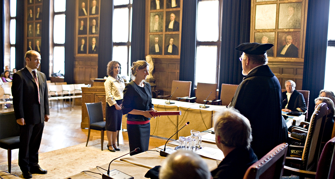 A PhD candidate receives her PhD at University Hall