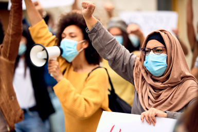 Muslim woman wearing protective face mask and supporting anti-racism movement on city streets.