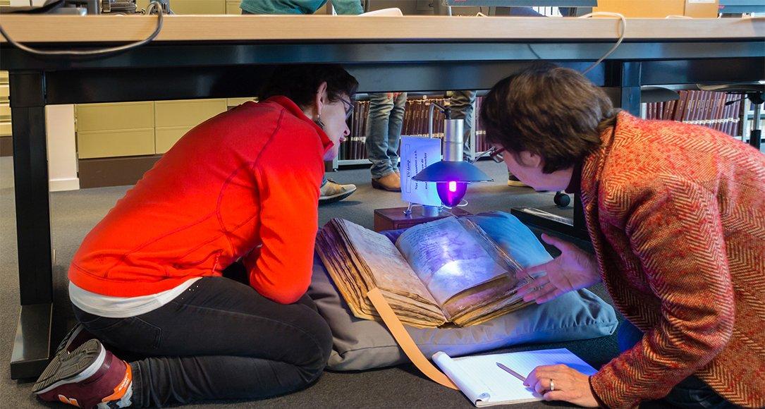 Bini Biemans (links) en Truus van Bueren (rechts) bestuderen het rekeningenboek onder een blauwe lamp. Een geïmproviseerde oplossing. Bron: verborgenschilderij.sites.uu.nl