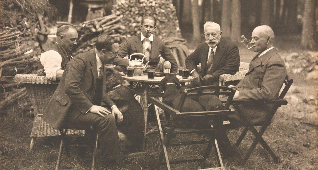 Theepauze bij de houthakkershut in het park van Huis Doorn, circa 1925. Van links naar rechts: majoor M.C. van Houten, dr. Viereck, Sigurd von Ilsemann, Wilhelm  II en generaal von Dommes (met sigaret). Op de stoel op de voorgrond zitten twee teckels.