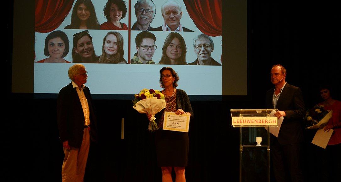 Dr. Mariëtte van den Hoven nam de scriptieprijs, bij afwezigheid van Naomi Alexander Naidoo (foto van Naomi linksbovenin op het projectiescherm), in ontvangst. Foto: Monique Lijster