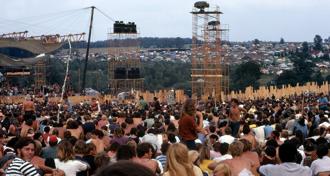 Woodstock Music and Art Fair. The person carrying the placard is Moonfire Lewis Beach Marvin III. Joe Cocker is performing on stage (17 August 1969). Source: Wikimedia/Woodstock Whisperer