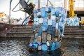 Duikers en bouwvakkers installeren het plastic op het geraamte van de walvis