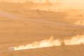 Auto werpt stof op in zinderende woestijn