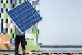 Werknemer monteert zonnepanelen op het dak van de Universiteit Utrecht.