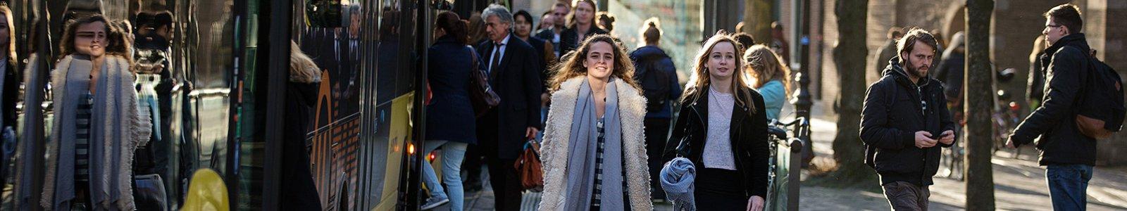 Mensen stappen in en uit bij een bushalte in Utrecht