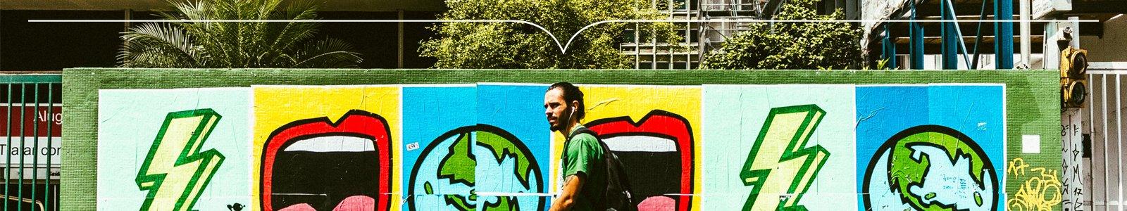 Man met oordopjes met snoertjes loopt langs muur met graffiti