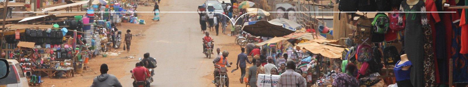 Markt en drukke zandweg met brommers en mensen in Afrika