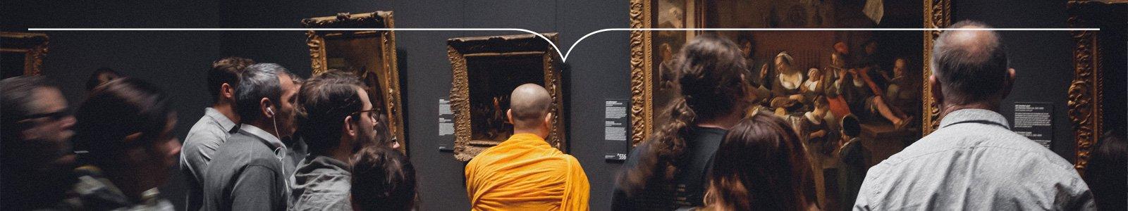 Kale monnik in oranje toga staat tussen toeristen voor een schilderij in een museum