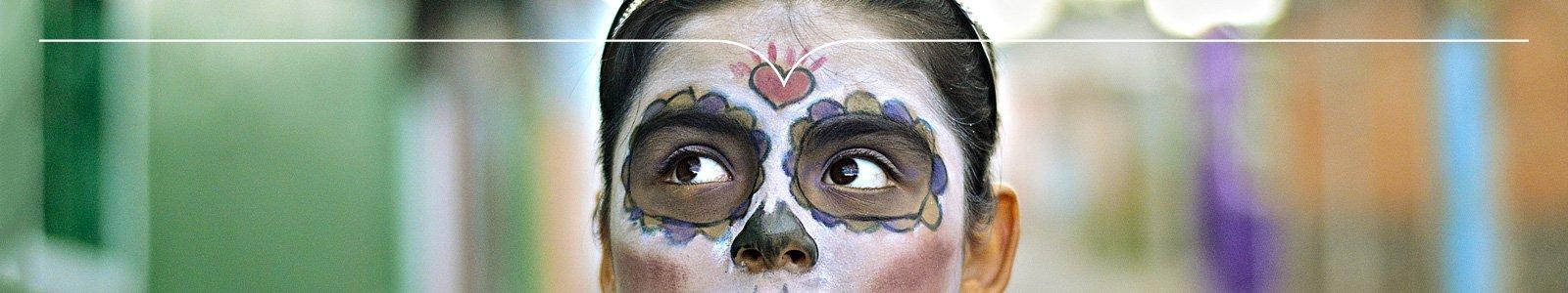 Vrouw met geschminkt gezicht kijkt nieuwsgierig opzij