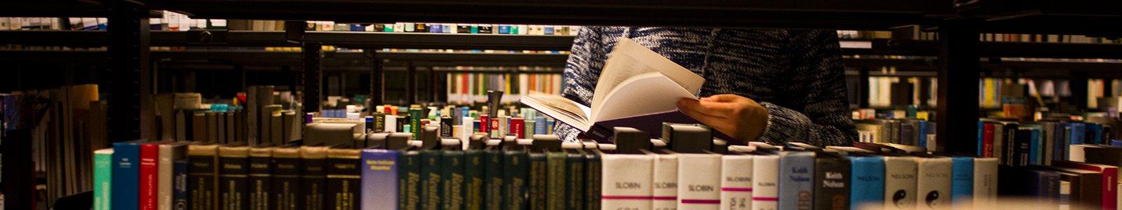 Student bladert door literatuur in de Universiteitsbibliotheek