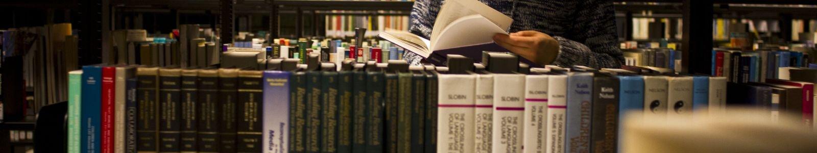 UB Uithof bladerende student met doorkijkje boekenplanken
