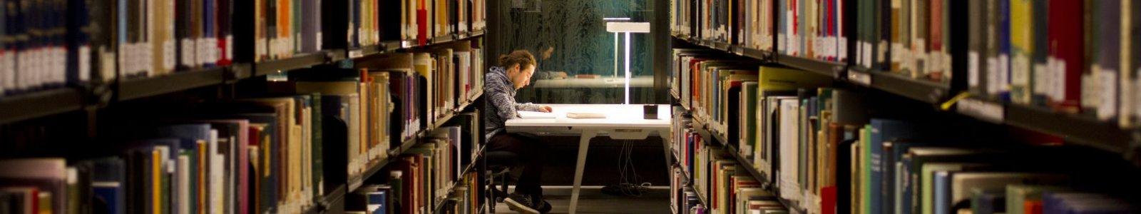 Student tussen boekenkasten in de UB Uithof