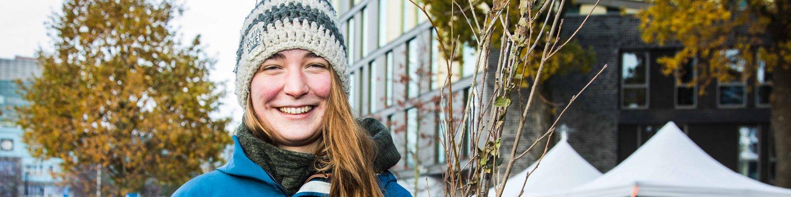 Studente met een warme muts, met een achtergrond van gebouwen, groene bomen en struiken