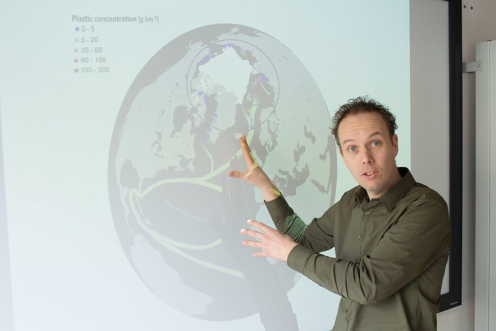 Erik van Sebille voor een scherm met afgebeelde oceaanstromingen
