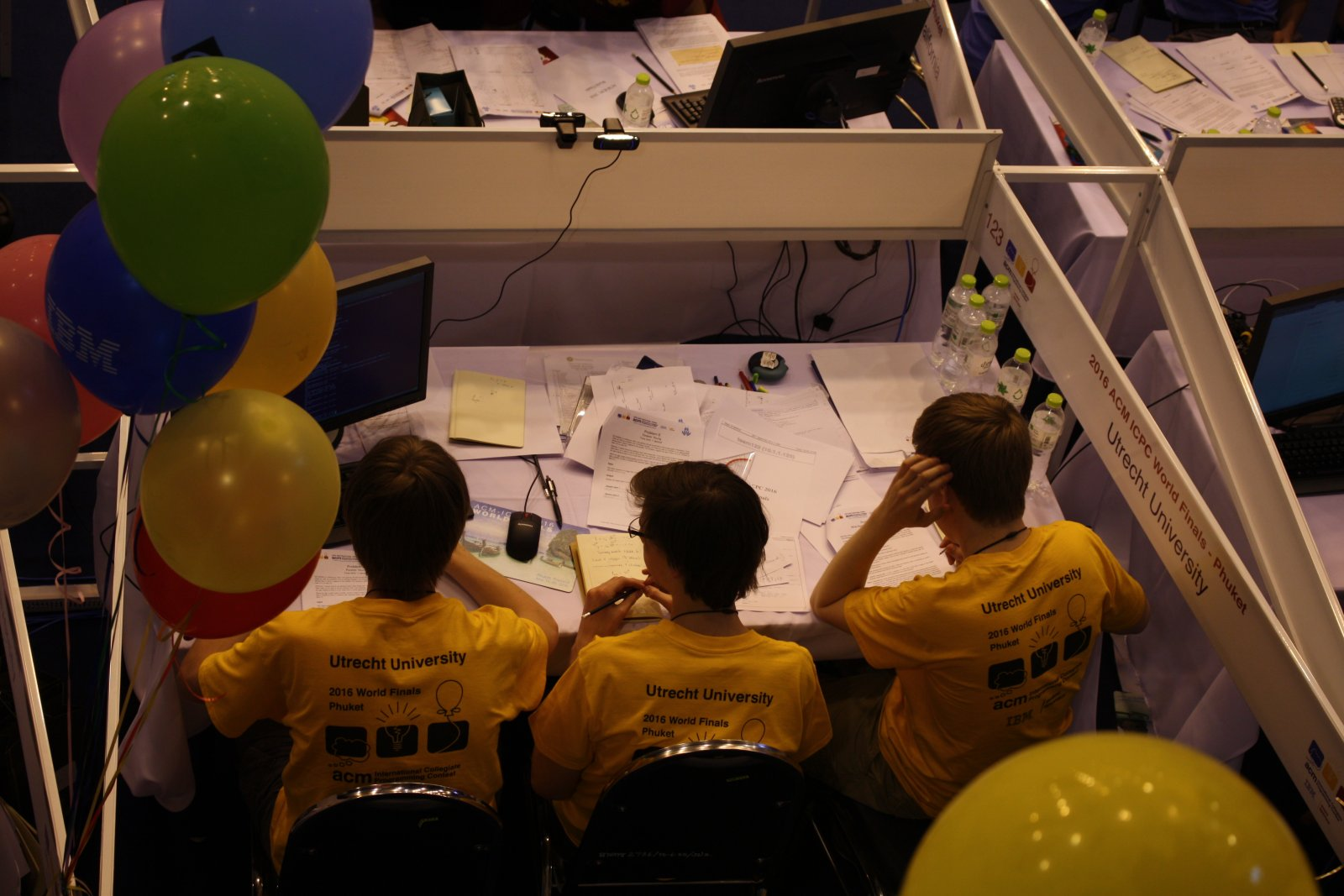 Het team tijdens de wedstrijd. Timon zit achter de computer, Harry en Ragnar werken opgaven uit op papier.