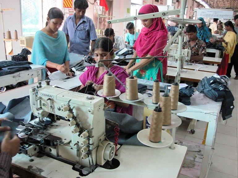 Women work in a textile factory outside Dhaka, Bangladesh. Source: Wikimedia/Mona Mijthab
