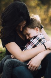 Moeder omhelst kind op schoot