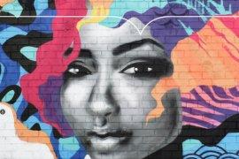 Graffiti op muur, vrouw met kleurrijk kapsel in afbeelding