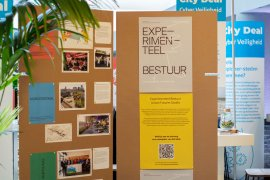 Cardboard display with different coloured posters about publication 'Experimental Governance' at 'Dag van de Stad 2019'