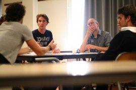 USE-studenten voeren een gesprek tijdens een werkcollege, waarbij de docent luistert.
