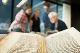 Docent bekijkt met studenten oude geschriften in de Universiteitsbibliotheek op De Uithof.