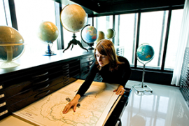 Studente bekijkt kaart in ladenkast waar wereldbollen op staan.