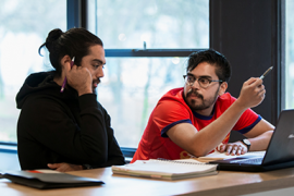Studenten werken samen achter de computer.