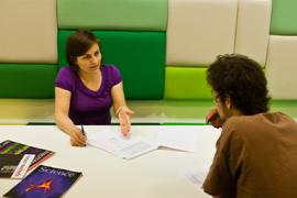 Mannelijke student voert gesprek met vrouwelijke voorlichter over studiemogelijkheiden.