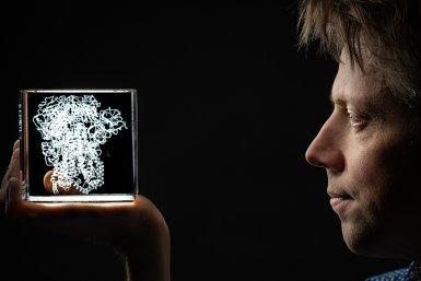 Onderzoeke Brend Jan Bosch kijkt in een model van een coronavirus dat in een doorzichtige kubus zit.