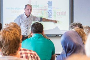 Groep mensen krijgt uitleg over de professionalisering van onderwijs