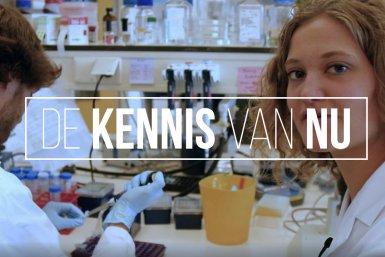 """Het Utrechtse iGEM team in het lab met logo van """"De Kennis van Nu"""""""