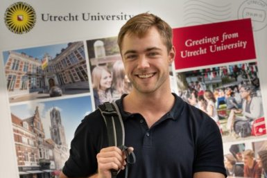 """A boy with a blue shirt in front of a large postcard saying 'Greetings from Utrecht University"""""""