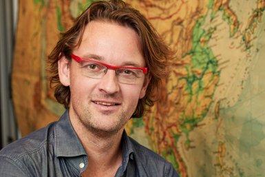 Vici ontvanger Douwe van Hinsbergen staande voor een kaart