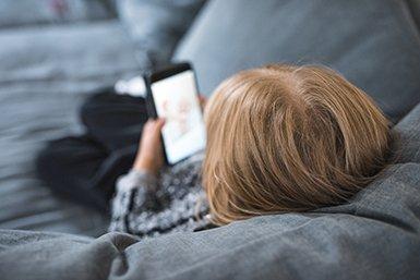 Jongere ligt op de bank met een telefoon