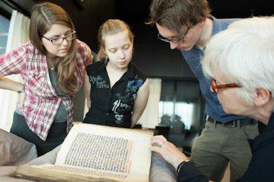 Studenten en docent bekijken middeleeuws handschrift in Universiteitsbibliotheek