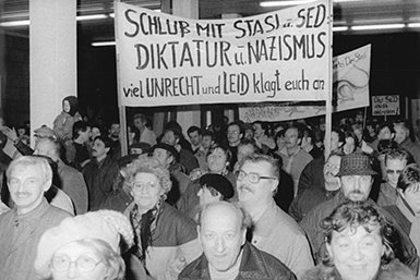 Citizens protesting and entering the Stasi building in Berlin; the sign accuses the Stasi and SED of being Nazi-like dictators. 1990. Bron: Wikimedia/ Bundesarchiv, Bild 183-1990-0116-013 / CC-BY-SA 3.0
