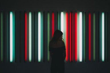 Vrouw in het donker, tegen neon verlichte achtergrond
