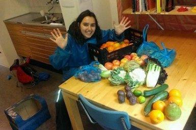 Een vrijwilliger van Taste before you waste met groenten op tafel