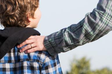 Hand van vader op de schouder van een kind.
