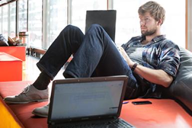 Student studeert met laptop op zitkussens in de Universiteitsbibliotheek in De Uithof.