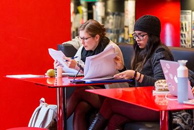 Studenten bekijken documenten op een studieplek bij de faculteit Geesteswetenschappen