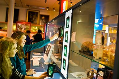 Twee meisjes kijken naar röntgenfoto's tijdens een tentoonstelling in het Universiteitsmuseum.