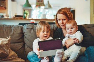 Een moeder en twee kleine kinderen met een tablet