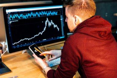 Een grafiek op een computerschermen een jongen met een smarthphone