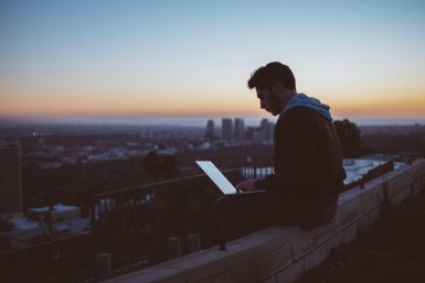 Jonge mannen met laptops buiten bij ochtendgloren
