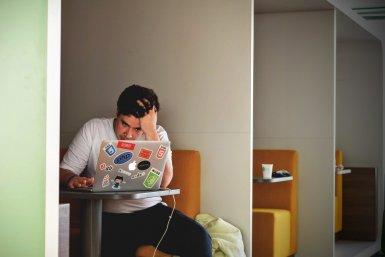 Jonge man achter laptop, grijpt in zijn haar