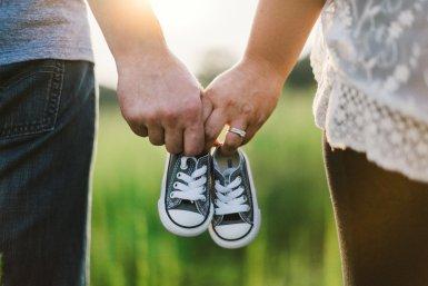 Ouders houden kinderschoenen samen vast
