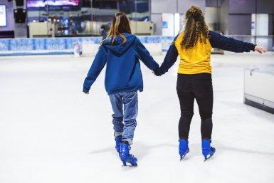 Twee meisjes schaatsen binnen op een ijsbaan