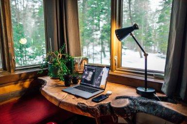Bureau thuis met uitzicht op bos en laptop aan